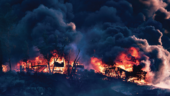 Fire scene of burning structures and clouds of smoke