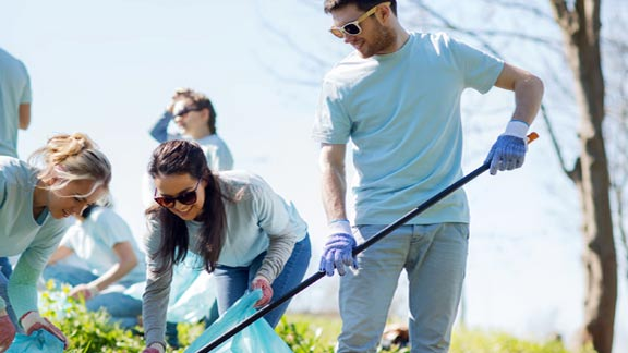 Young adults raking debris