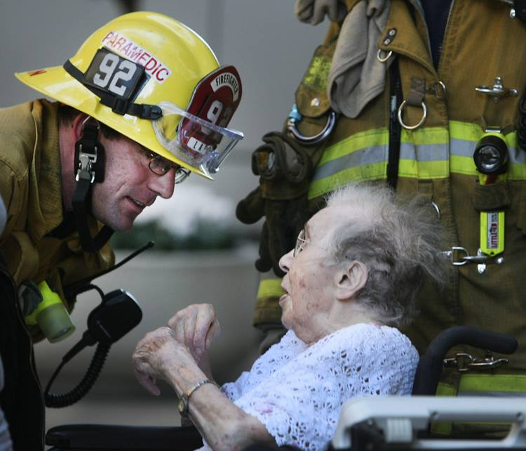 Firefighter comforting older woman.