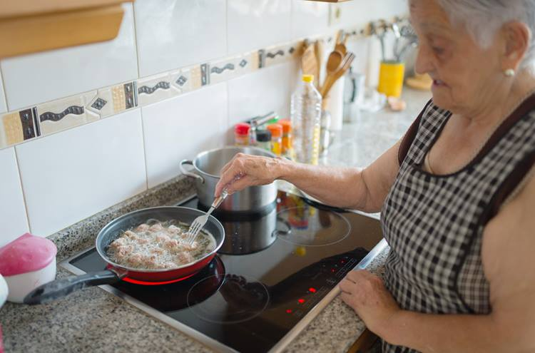 Older woman cooking on electric oven.