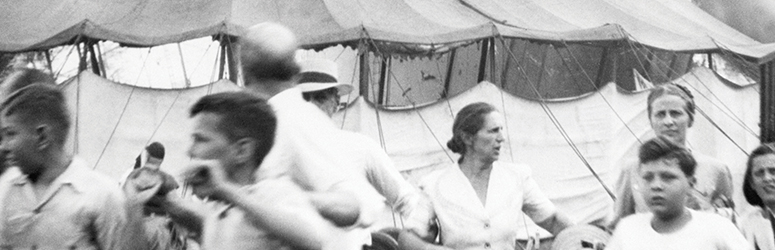 Black and white photograph of people fleeing a circus tent