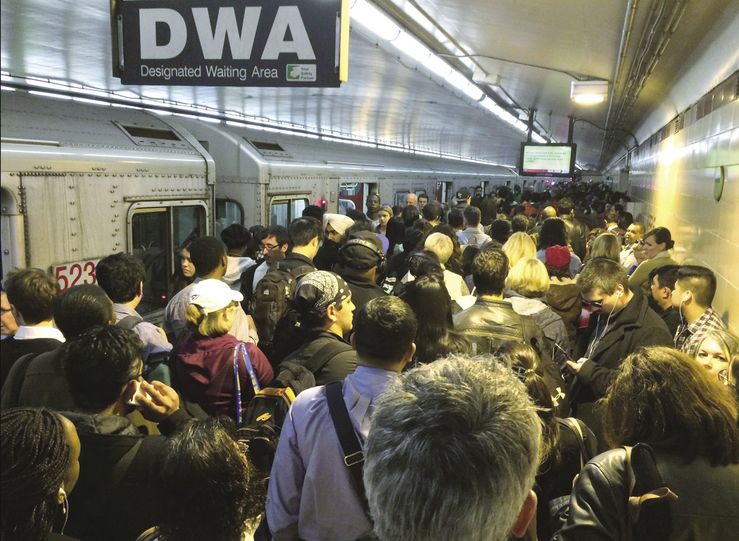 Commuters in Toronto crowd onto a platform after fire affected one of the city's subways stations in May.