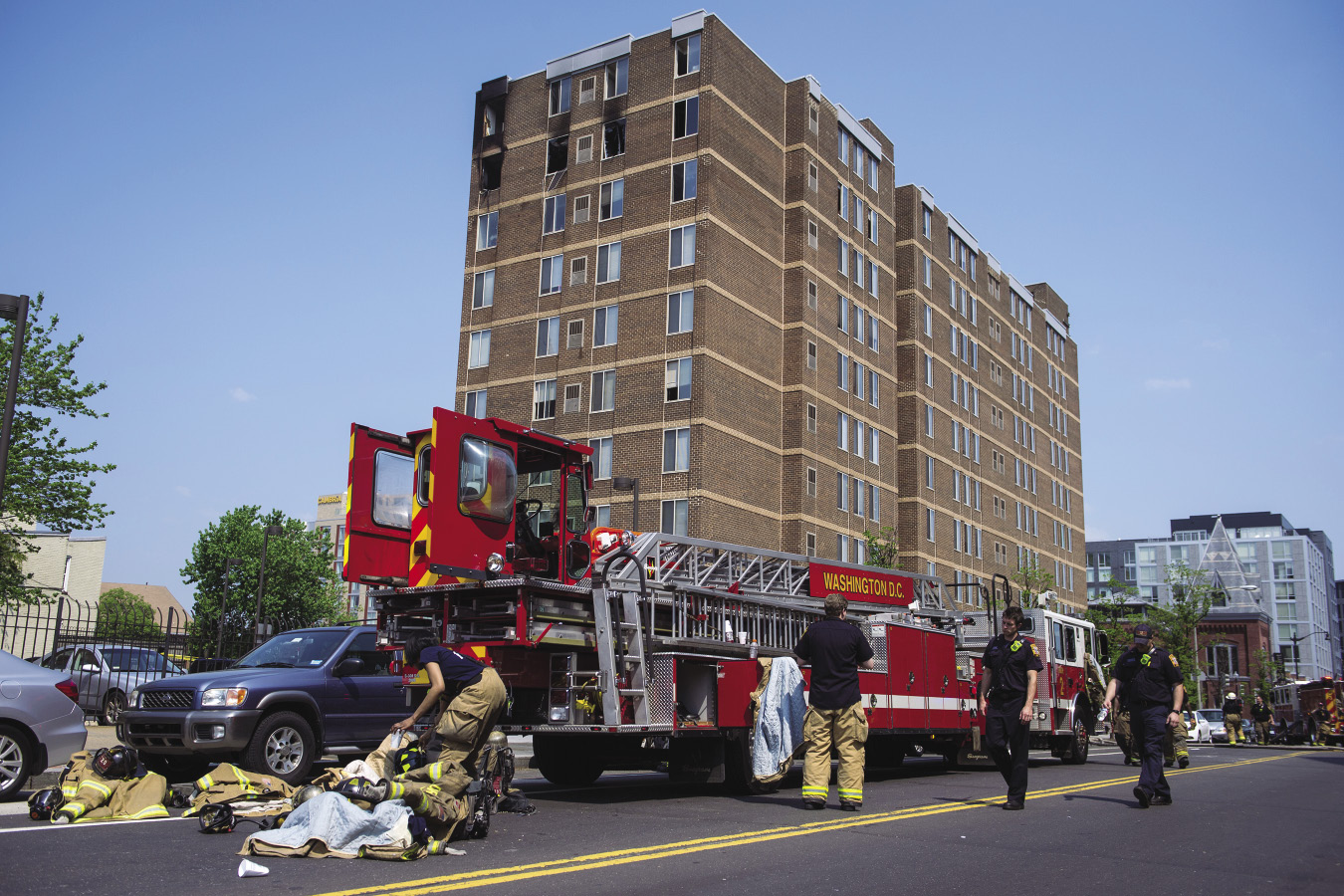 Firefighters change next to an fire apparatus that is parked next to a high rise apartment building
