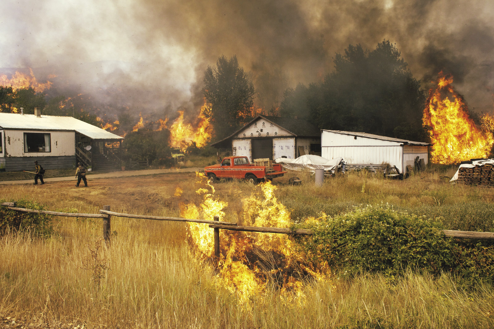 Firefighters attempt to protect a home and outbuilding from a wildfire in Washington state.