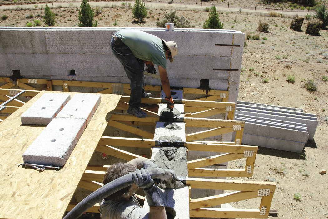 Workers pump concrete into insulated concrete forms that make up the exterior walls of the home
