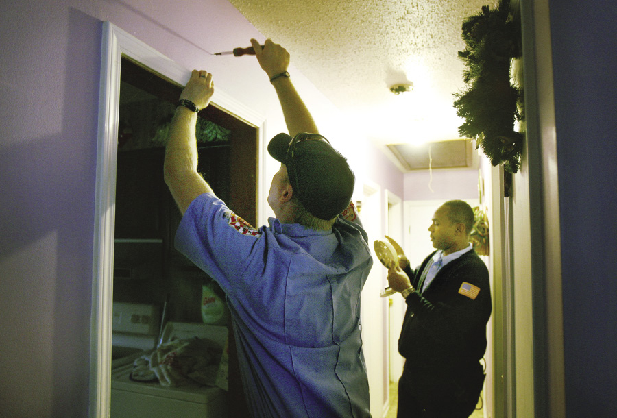 Firefighters helping to install fire alarms in residential home