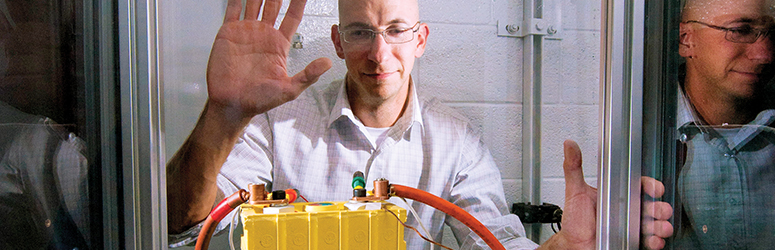 Man looks at an energy storage system in a glass box.