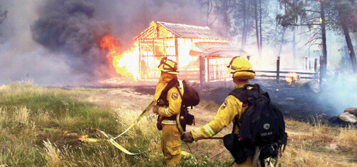 Two wildland firefighters watch as a house burns due to a forest fire.