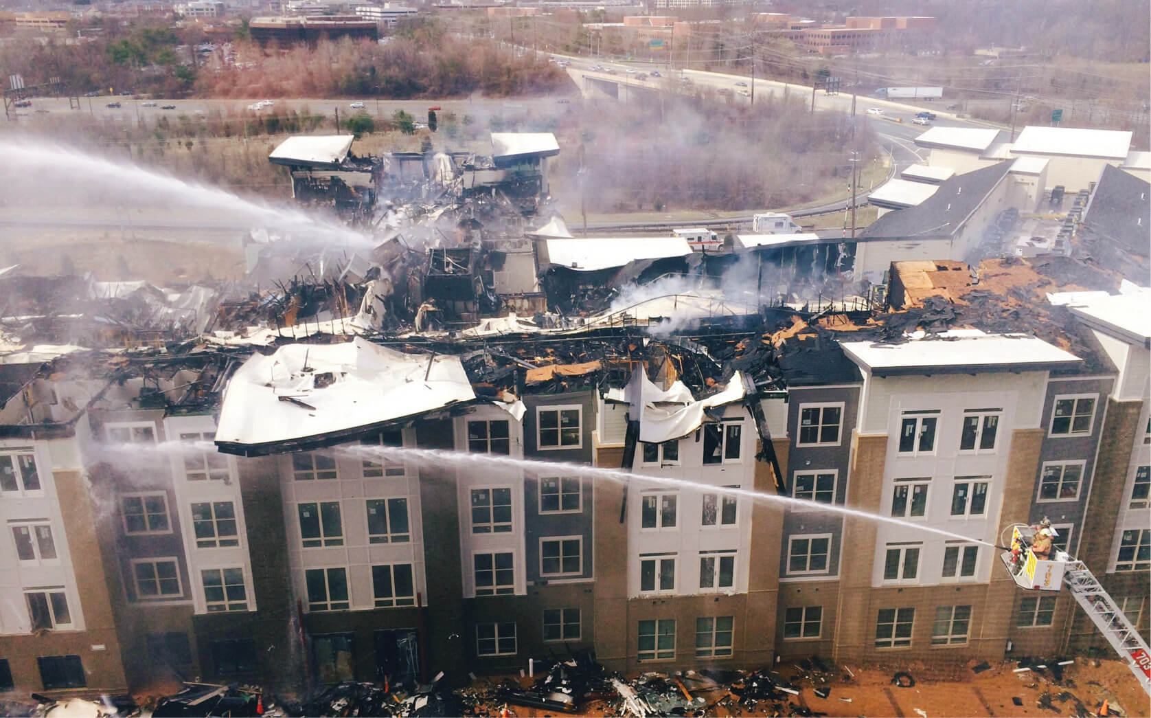 Multiple firefighters battle an active fire in the roof of a apartment complex.