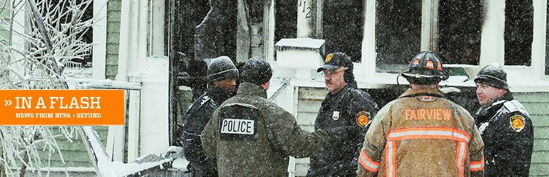 Firefighters and police stand outside a burnt house in the snow