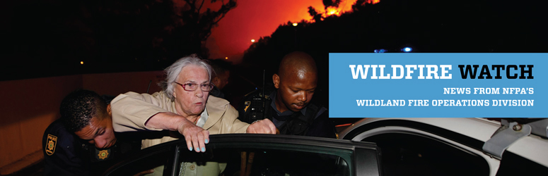 Elderly woman being escorted into a police car while wildfire glows in the background