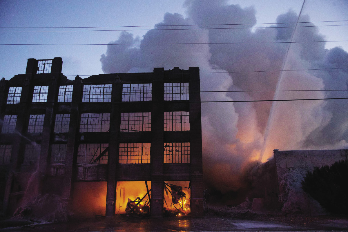 A warehouse burns at dust while firefighters attack with water
