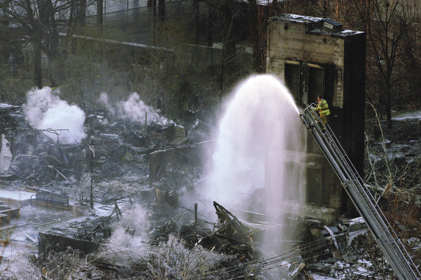 Firefighters put water on the remains of an apartment complex destroyed by a fire