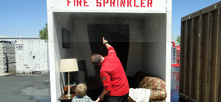 Man and child look at a sprinkler in a burn demo booth