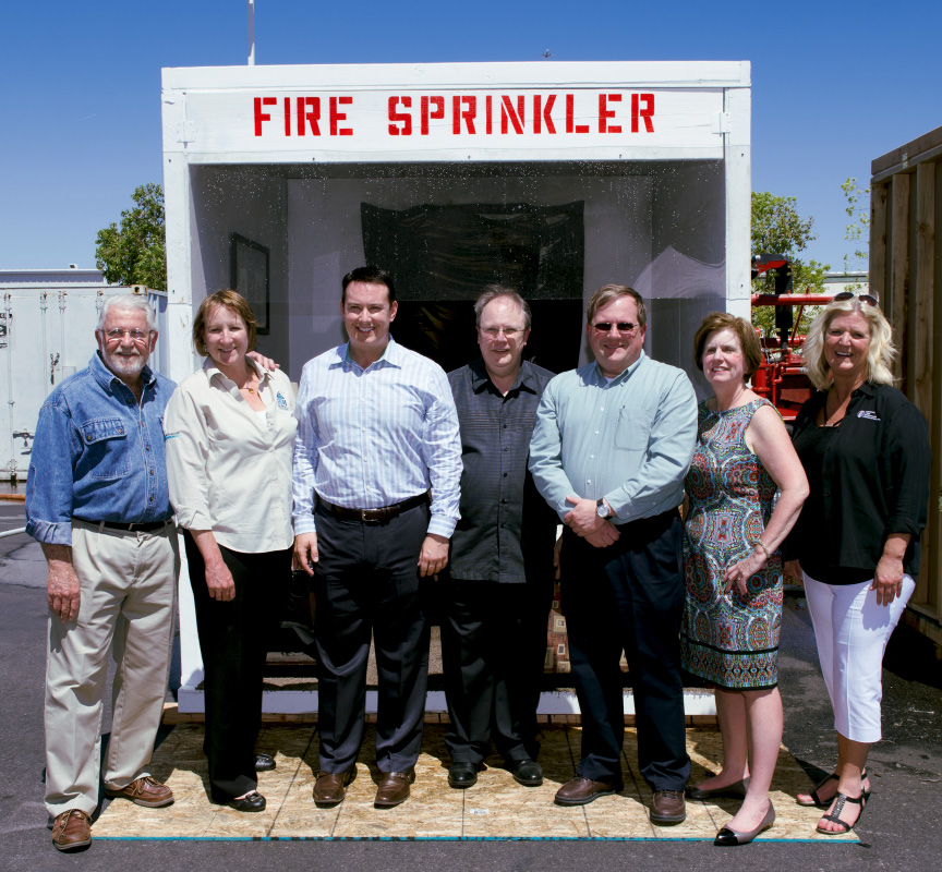 Home Fire Sprinkler Coalition Founders standing in front of a sprinkler demo booth.