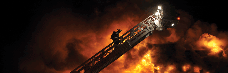 Firefighter climbs ladder while fire rages in the background