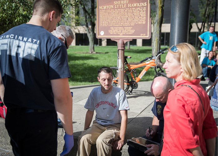 Firefighters talk to a man who identified himself as an addict and asked for help at a heroin awareness rally in Cincinnati.