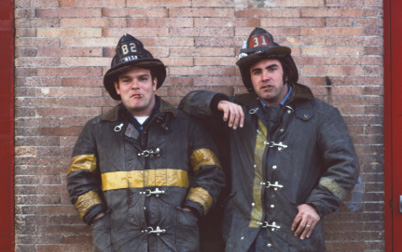Two firefighters pose for a photo, both have dirty gear on.