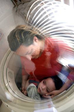 Woman with her comatose son undergoing hyperbaric oxygen treatment.