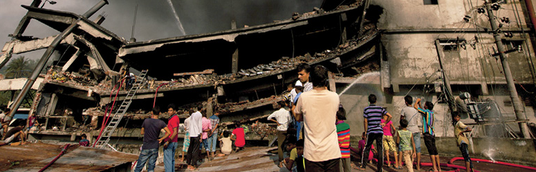 People look at the aftermath of a packaging factory fire in Bangladesh.
