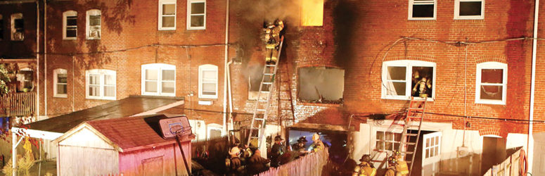 Large group of firefighters attack an active fire in a rowhouse in Delaware.