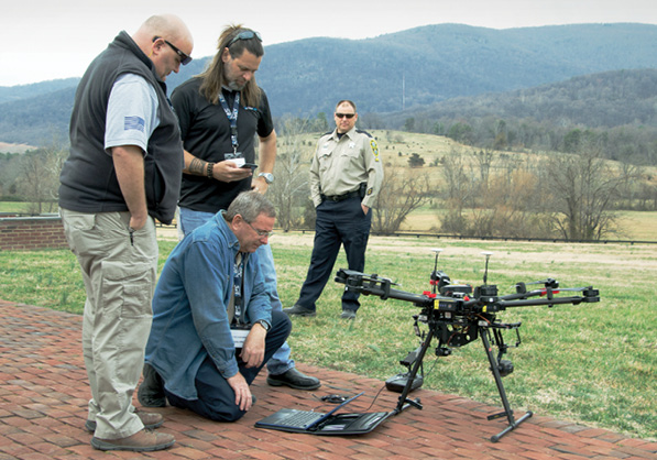 Men look at a drone on the ground