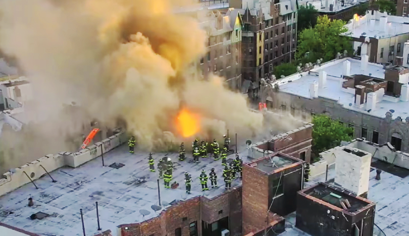 Firefighters train on a rooftop while a drone films from above.
