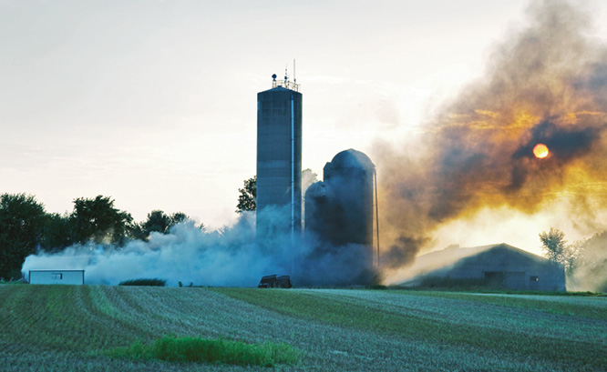 Smoke pours out of a farm fire.