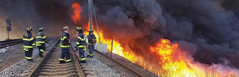 Wildland firefighters on a railroad track prepare to attack a raging wildland fire.