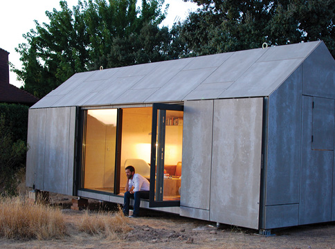 Grey Tiny Home with man on door sill.