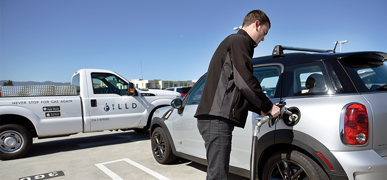 Man fuels up his car in a parking lot with the help of a mobile fueling company.