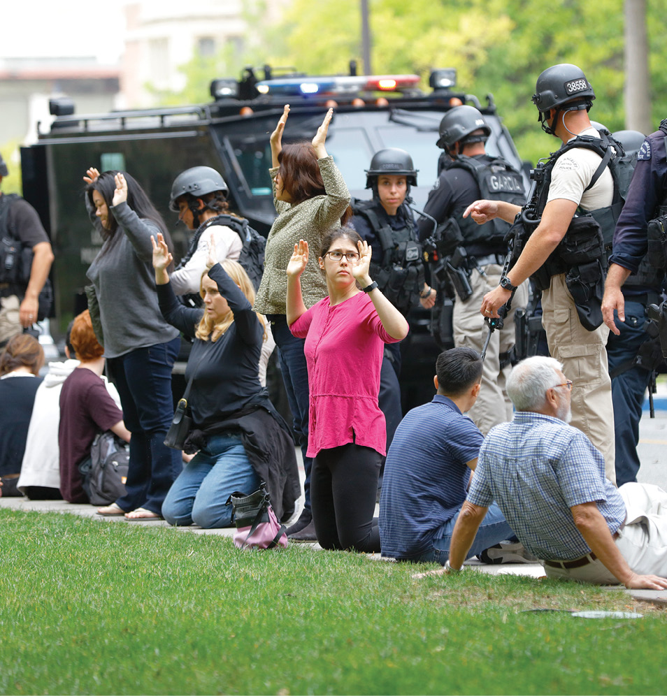 People sit down on a sidewalk with arms up as police officers respond to reports of a campus shooting at UCLA.