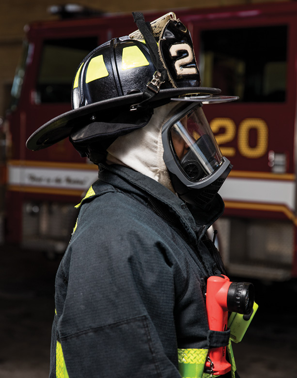 Side profile of a firefighter in turnout gear showing how protective hoods are worn under the helmet and mask to cover the face and neck.