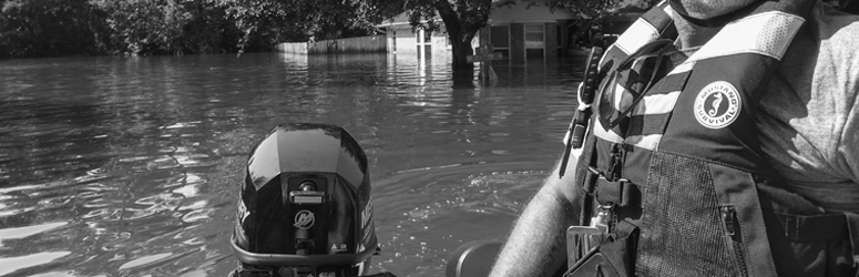 Man drives boat away from flooded home