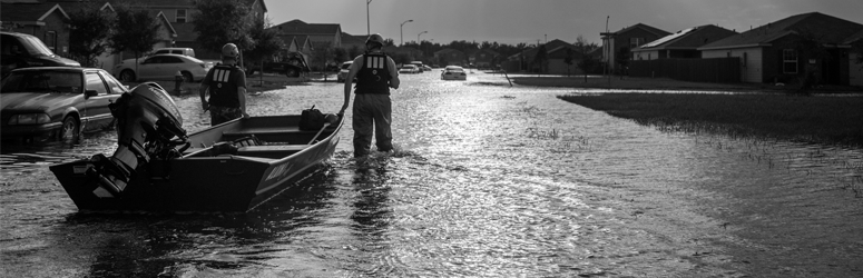 Men walk through flooded neighborhood with boat