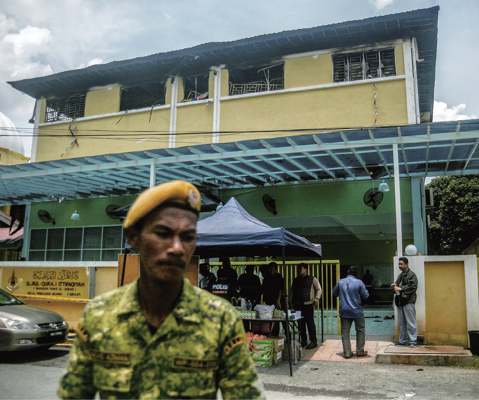 Military man stands guard outside school in Kuala Lumpur that experiences a deadly fire.  The top floor of the school has broken windows and is in disarray.