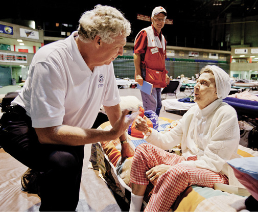 Richard Serino talks with a flood victim in an emergency shelter