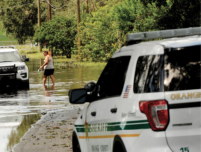 Police cars sit in flood water as woman walks up to car
