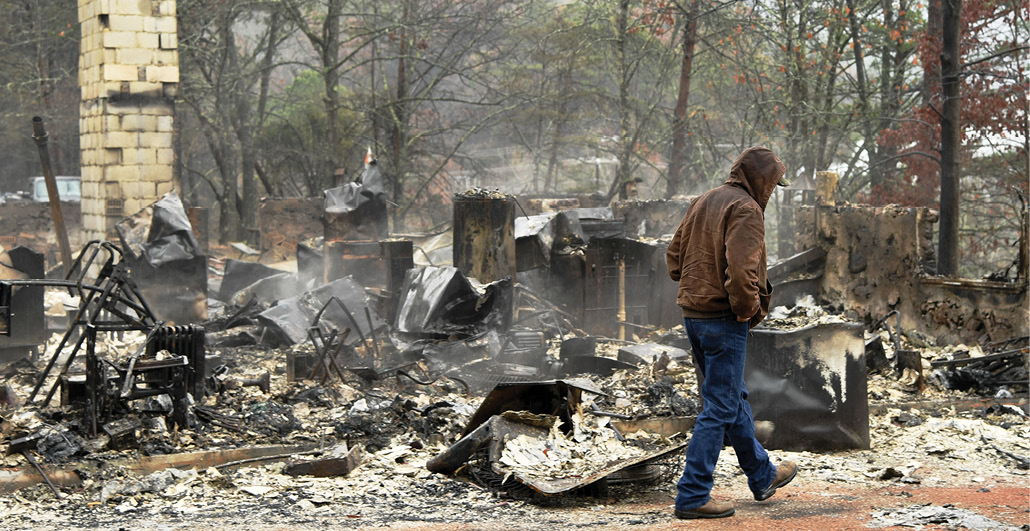 Man walks past the remains of his home after a wildfire