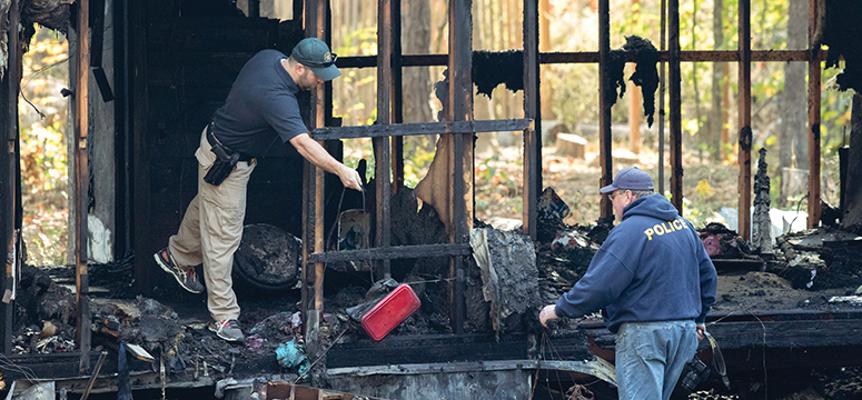Two fire investigators clean out the remains of a home fire.