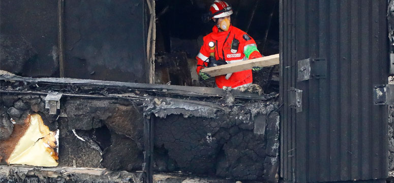 Members of the emergency services work on the middle floors of the charred remains of the Grenfell Tower block in Kensington, west London