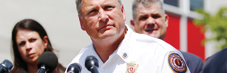 Fire Chief looks solemn while speaking into a news microphone at a podium