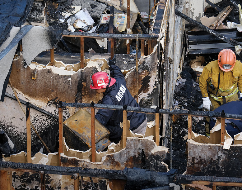 Arson investigators in California examine the ruins of a vacant office building where a fire killed five people.