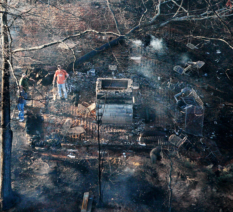 Man stands in the remains of a home that was destroyed by wildfire in November.