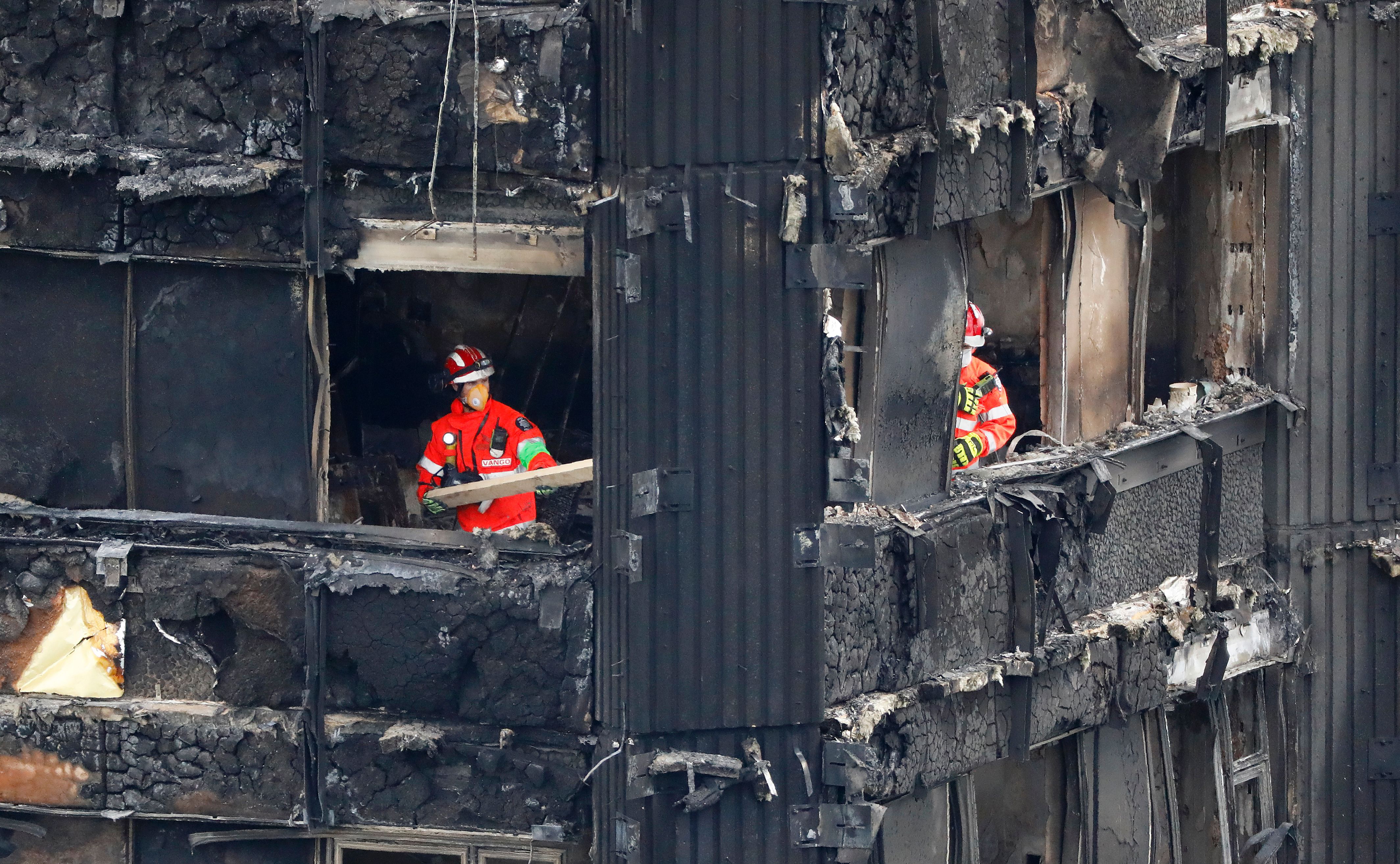 Members of the emergency services work on the middle floors of the charred remnains of the Grenfell Tower block in Kensington, west London