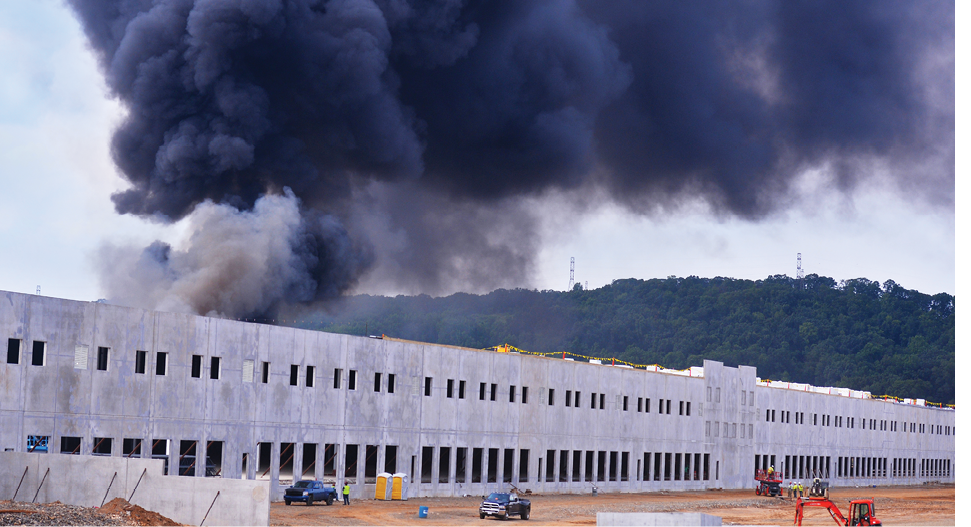 Fire rages in a large warehouse under construction.