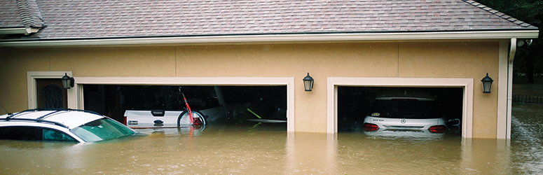 Residential home submerged in flood water with three cars partial covered