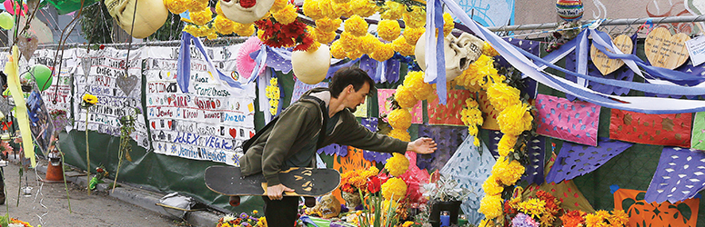 Man places flowers at memorial site of the Ghost ship fire