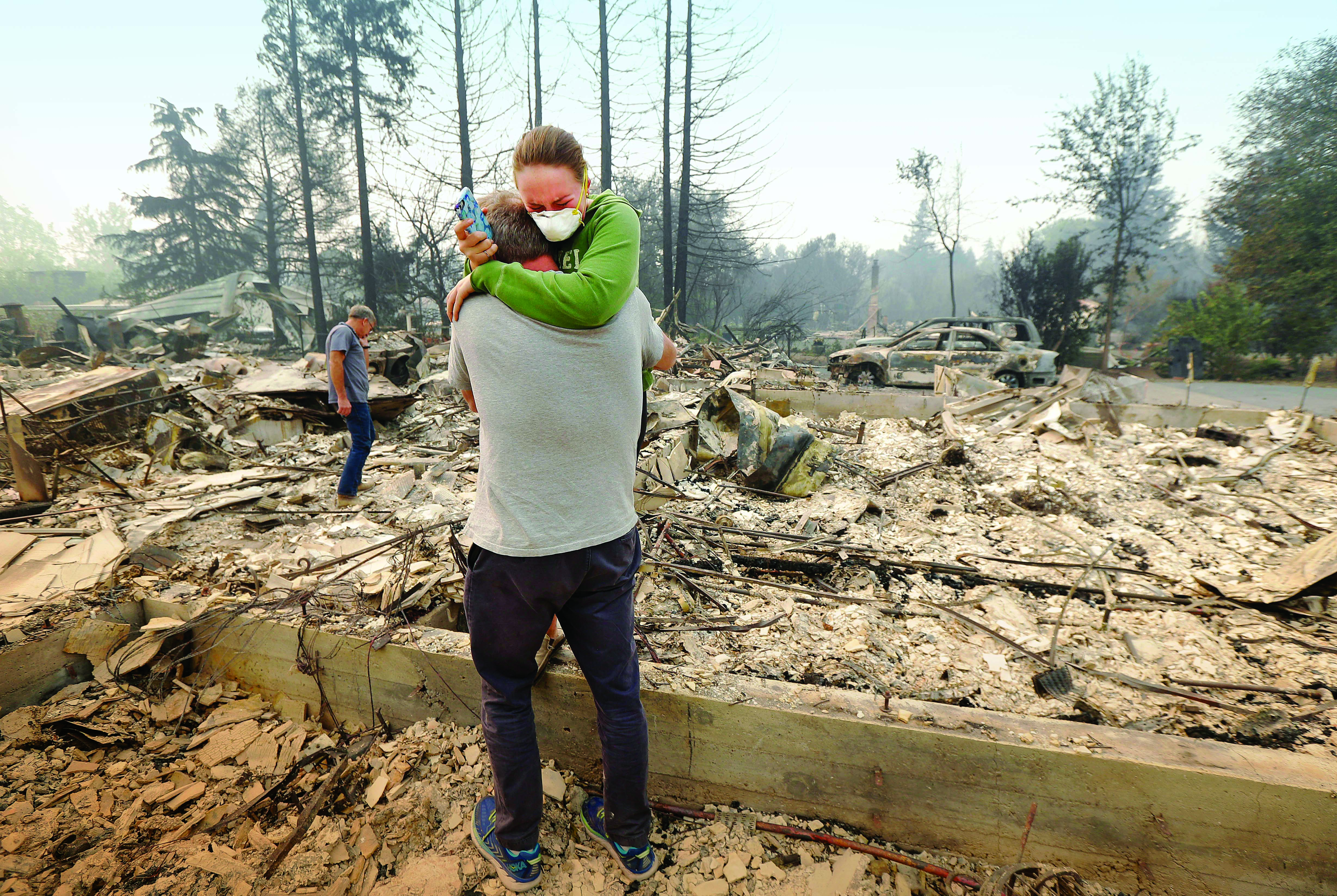 Man comforts a woman after a wildfire destroys their home