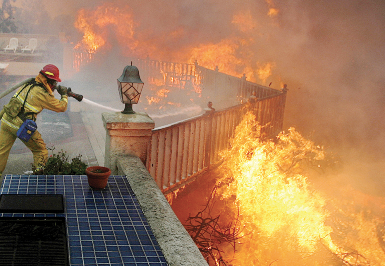 Wildland firefighter battles a raging wildfire on the porch of someones house